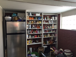 The room was dark with open pantry shelves and not enough storage.
