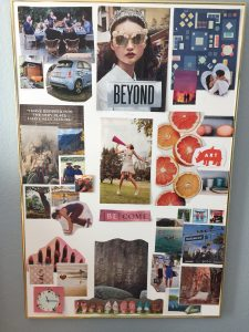 A completed vision board with cut out images from magazines, photos, postcards and maps placed on a white poster board organized by the 8 feng shui bagua areas.